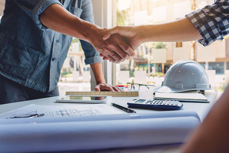 Business Insurance - Closeup View of a Business Handshake in an Office Over a Table with Construction Blueprints a Calculator and a Hard Hat