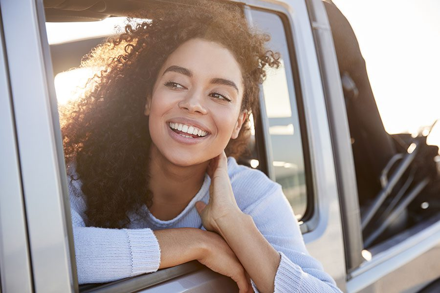 Contact - Portrait of a Young Smiling Woman Sitting in a Car Sticking Her Head Out the Window to Look Around