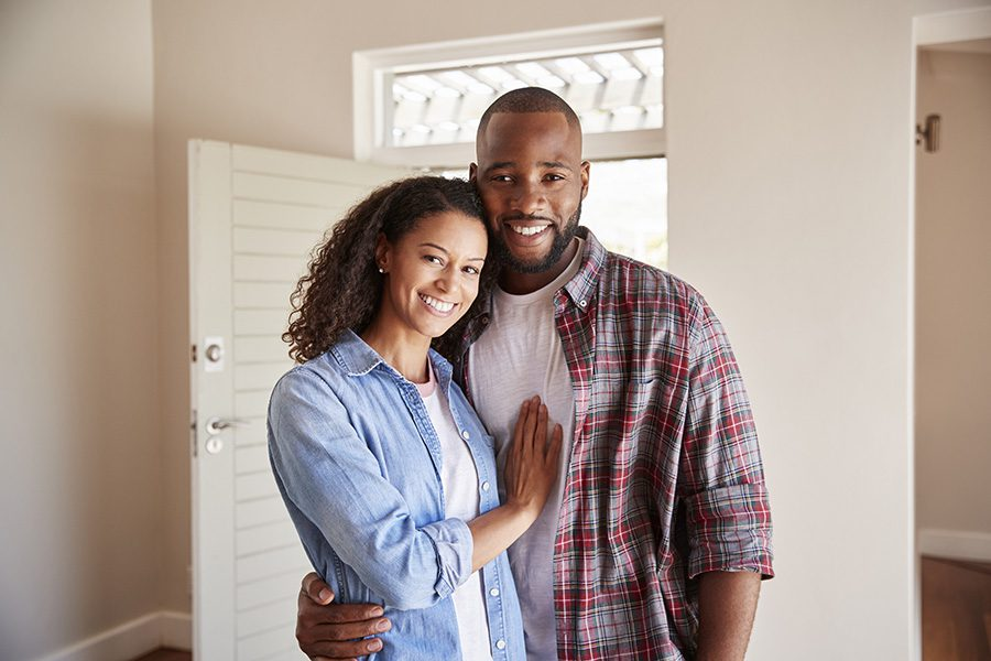 Insurance Quote - Portrait of a Cheerful Young Married Couple Standing Inside Their New Home