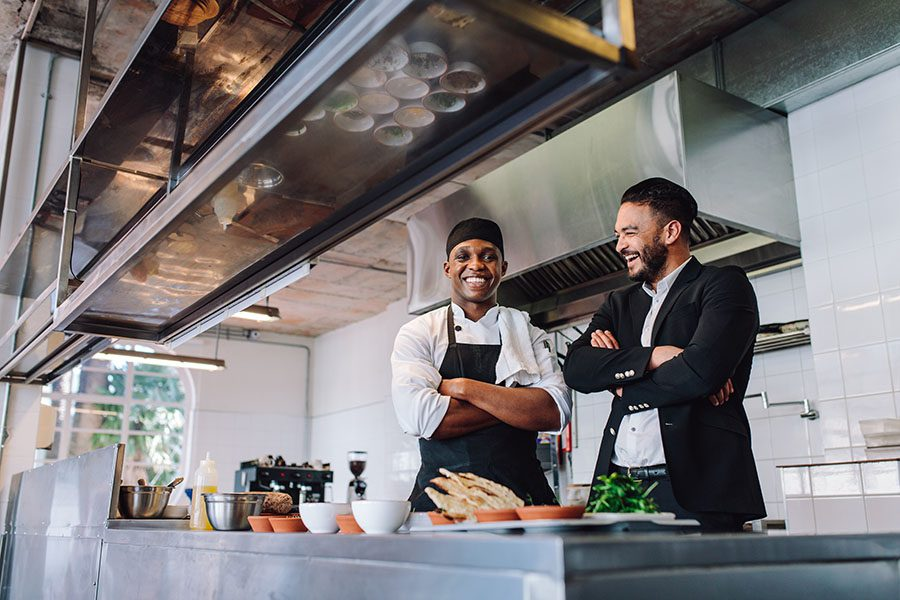 Specialized Business Insurance - View of a Smiling Restaurant Manager and Cook Standing Behind the Counter in the Kitchen of a Restaurant