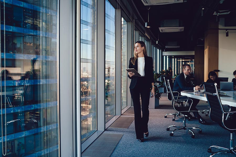 Business Insurance - Woman Looks Out the Window From a High Rise Office Building, Holding a Tablet, Employees at a Conference Table Behind Her