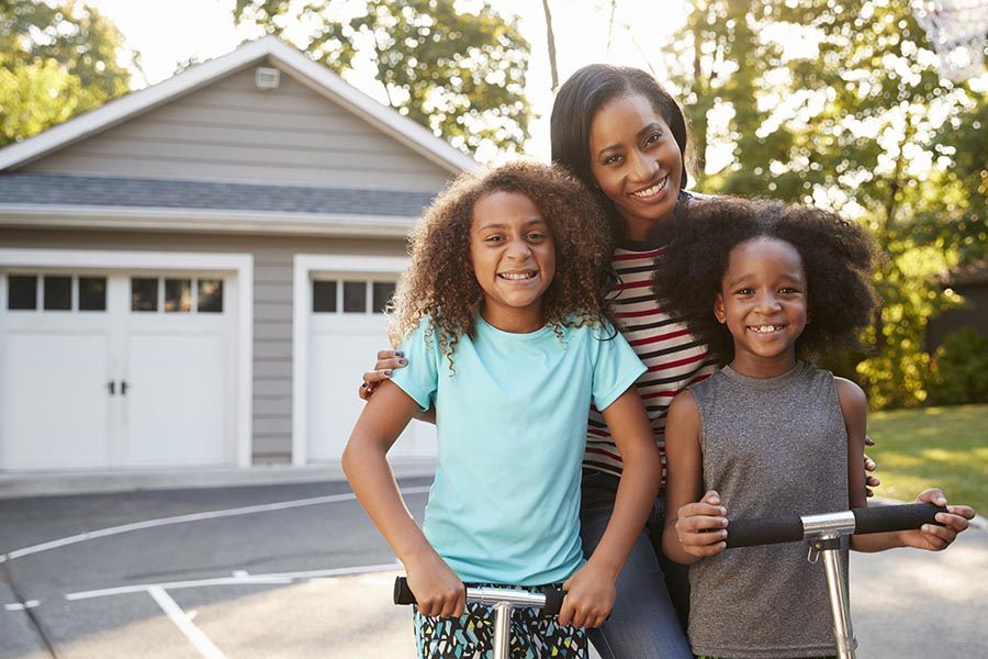Personal Insurance - Mother and Young Daughters Smile in Their Driveway, Detached Double Garage Behind Them, the Girls Standing on Scooters
