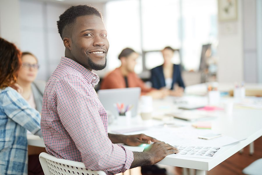 Business Insurance - Portrait of Young Man Smiling at Camera While Sitting at Table in a Business Meeting