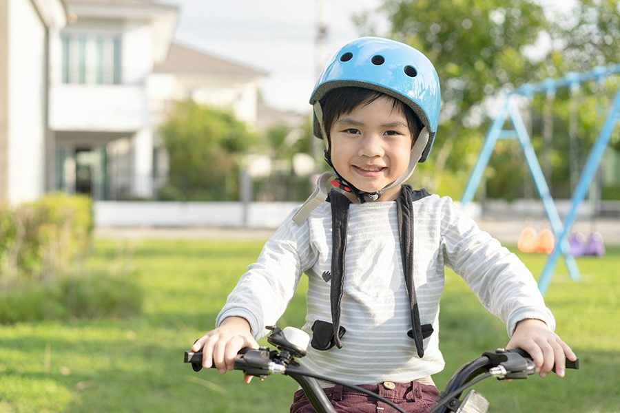 Employee Benefits - Smiling Boy in Safety Helmet Riding His Bike in the Park