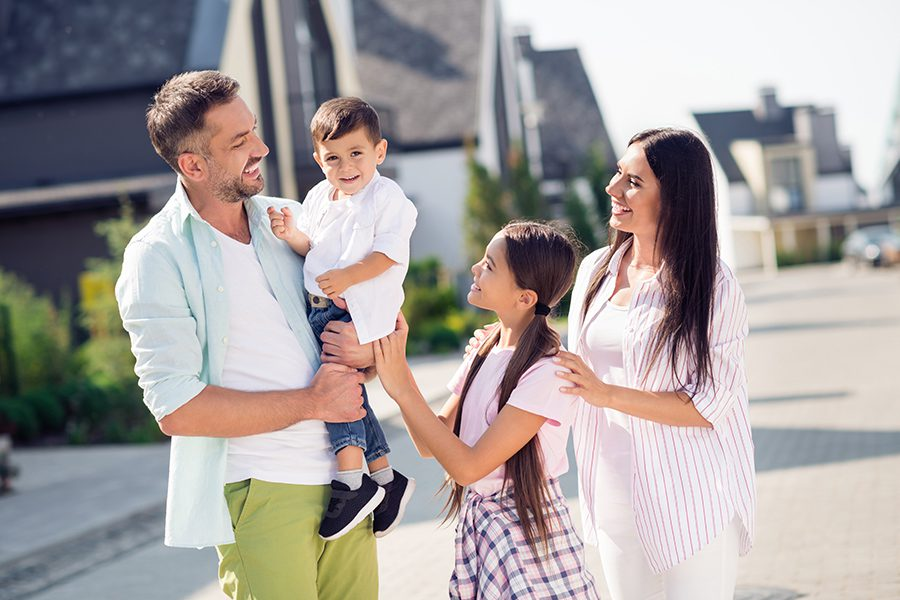 Personal Insurance - Happy Family Looking at Youngest Child Walking Outside Near Their Home