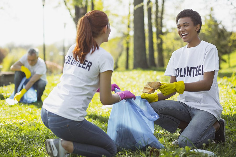 Specialized Business Insurance - Two Optimistic Volunteers Holding Garbage Bag in the Park on a Summer Day
