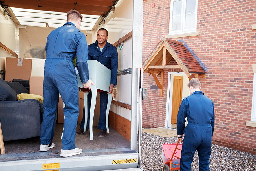 Moving Company Insurance - Moving Company Workers Unloading Furniture And Boxes From Truck Into New Home On Moving Day