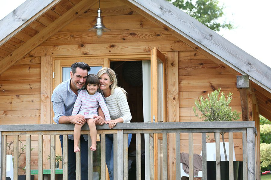Personal Insurance - Closeup View of Two Smiling Parents and Their Daughter on the Front Balcony of a Wooden Home