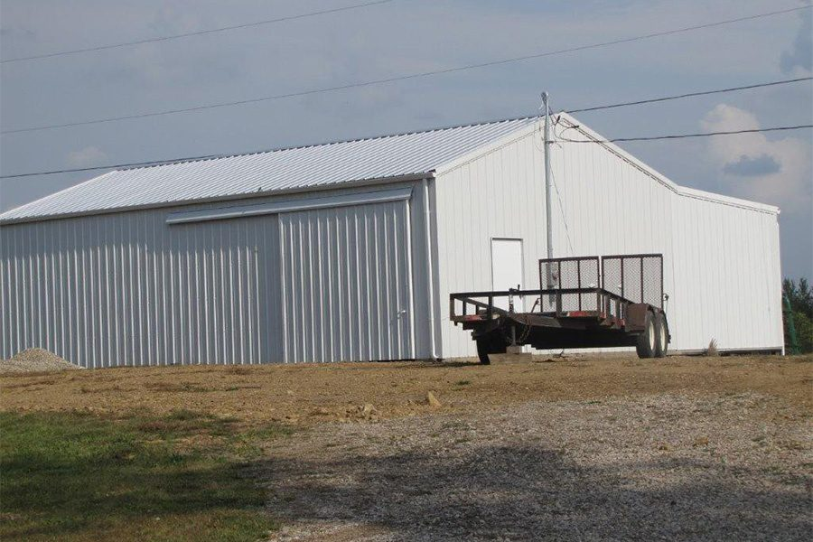 Contact - View of Metal Storage Building with a Trailer Next to It on a Farm Setting in Ohio