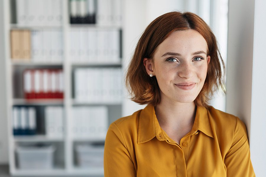 Business Insurance - Focus of Happy Young Businesswoman with Background of the Office Blurred