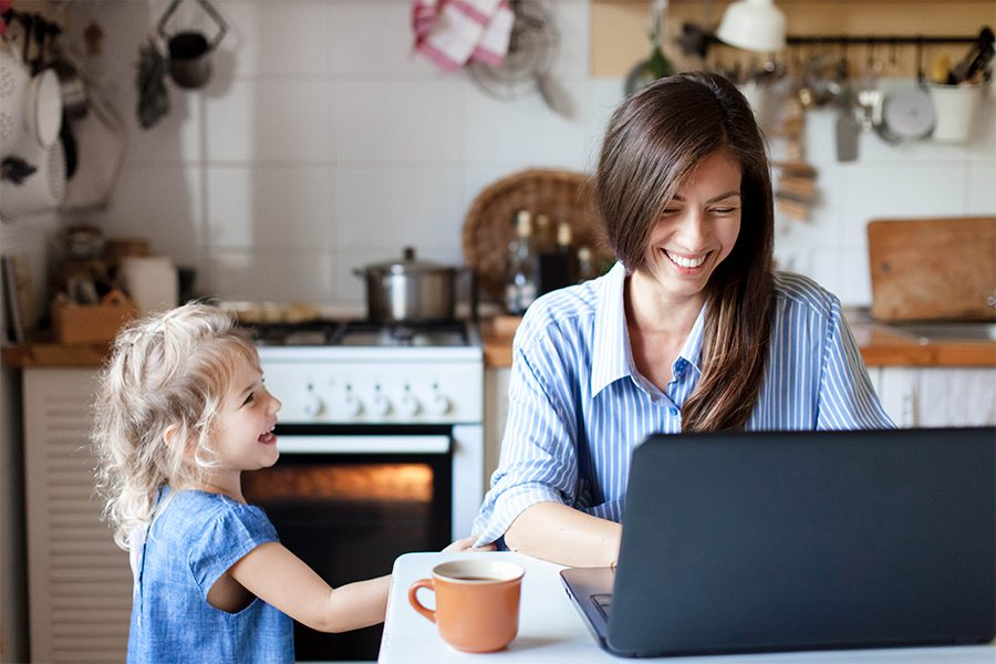 Blog - Mother and Young Child in the Kitchen While Mom is Working on Her Laptop