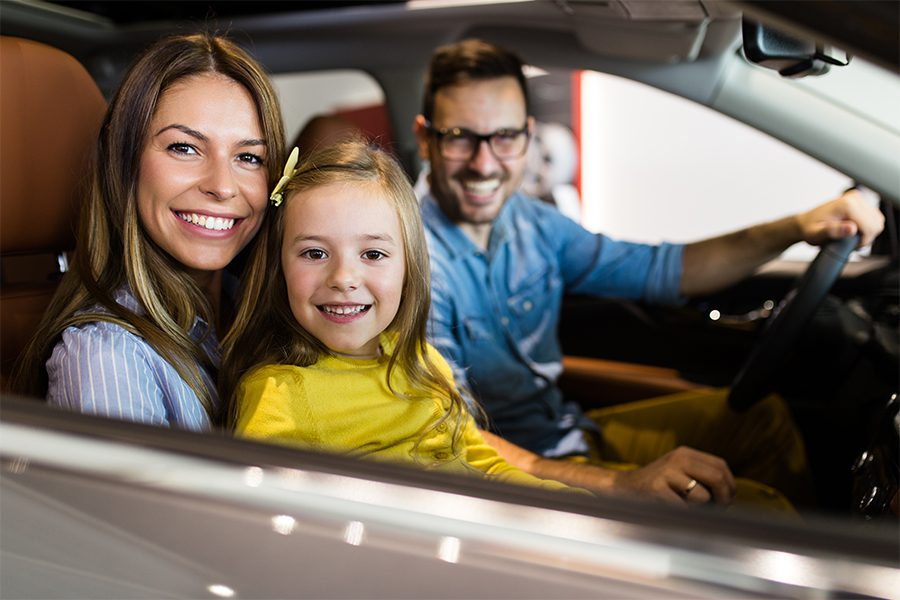 Personal Insurance - Happy Family Sitting in New Vehicle and Getting Ready to Drive Out of the Dealership