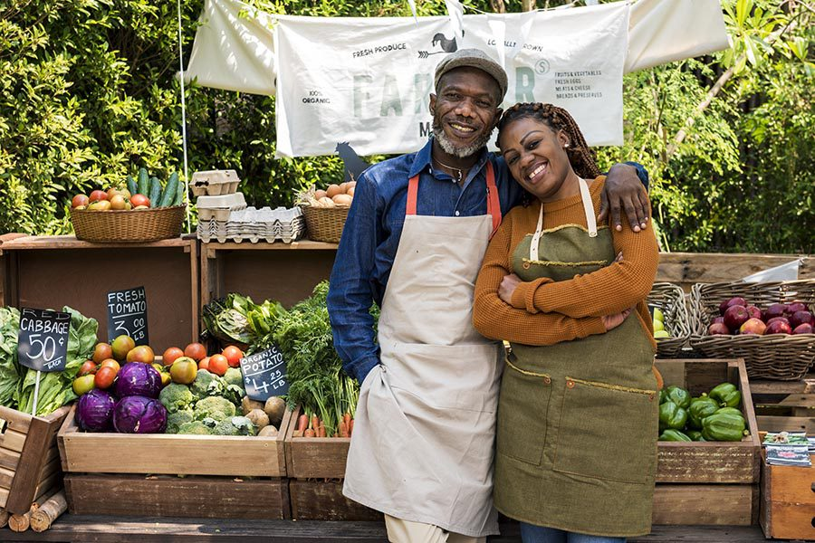 Business Insurance - a Couple Selling Produce at a Farmers Market Food Stand, Smiling and Wearing Work Aprons