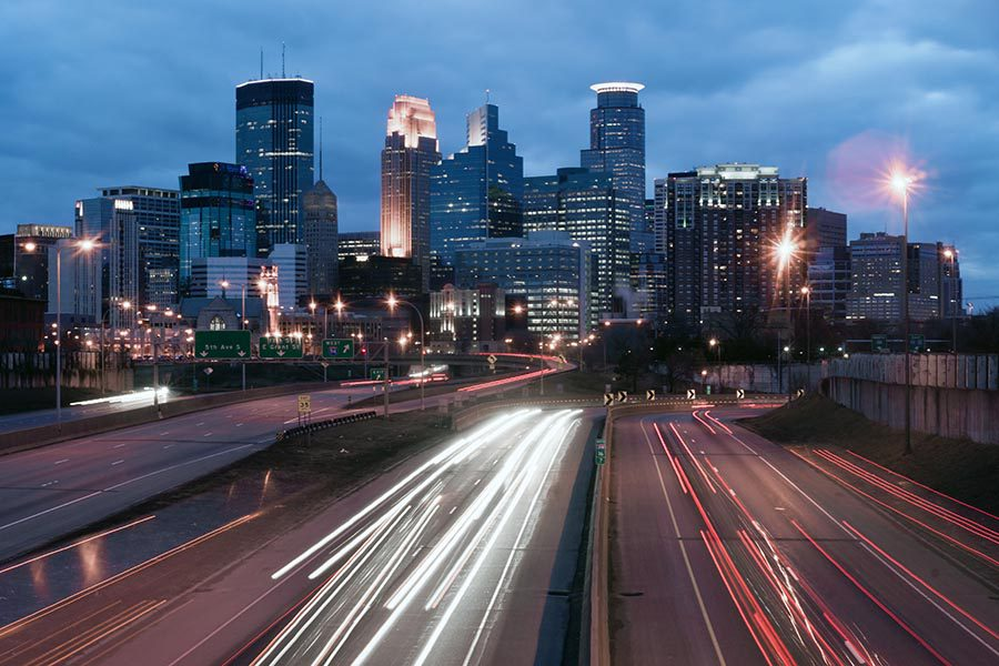 Contact - Long Exposure Image of Minneapolis, Minnesota Seen From the Highway, With Cars Zooming in and Out of the City, and the Buildings Lit up for the Evening