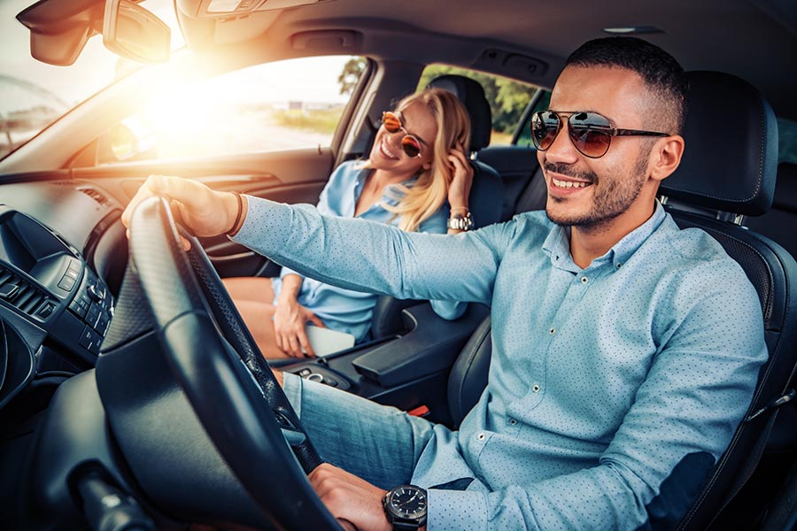 Personal Insurance - a Couple Driving in Their Car on a Sunny Day, Smiling and Wearing Blue Shirts and Sunglasses