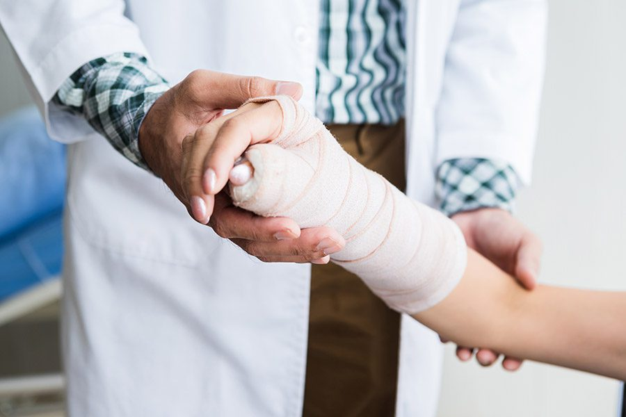 Group Accident Insurance - Woman Holding Up her Broken Arm with a Doctor Adding a Cast