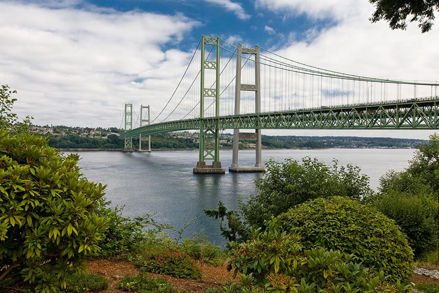 About Our Agency - Tacoma Narrows Bridge on a Sunny Day With Greenery in the Foreground