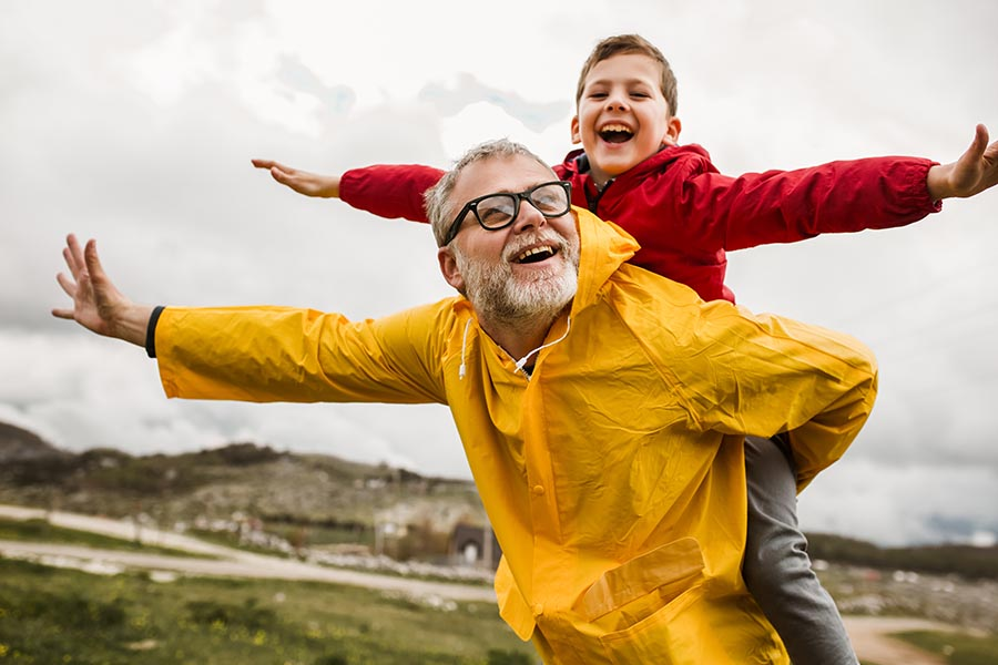 Personal Insurance - Young Boy Rides on His Grandfather's Back, Both Dressed in Rain Coats as They Walk Through a Green Landscape in the Rain