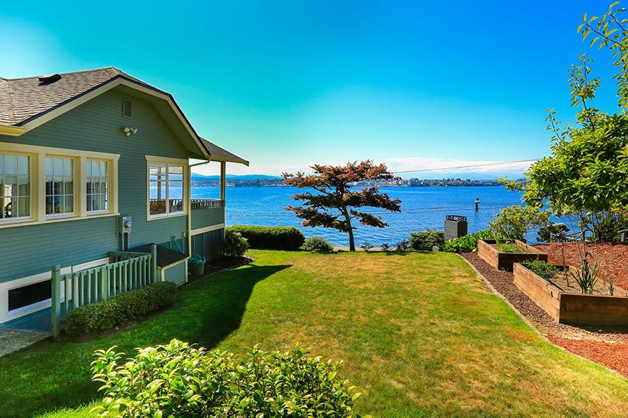 Port Orchard, WA Insurance - Green Home on a Grassy Yard Overlooking Blue Water on a Cloudless Day