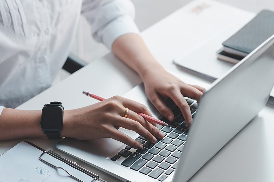 Resources - Business Woman Typing On Her Laptop At Her Desk with a Pencil in Hand