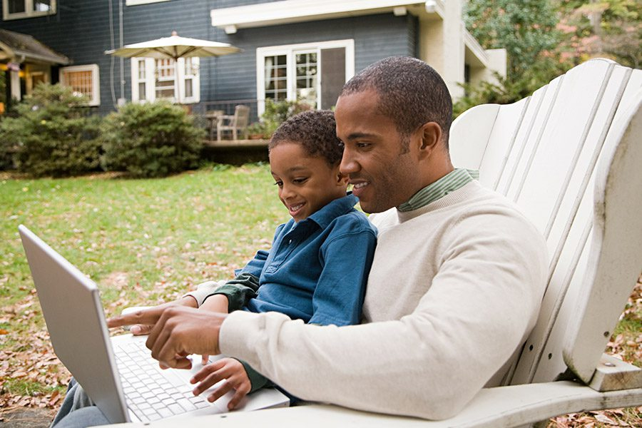 Client Center - Father and Son Using Laptop in Front of Home