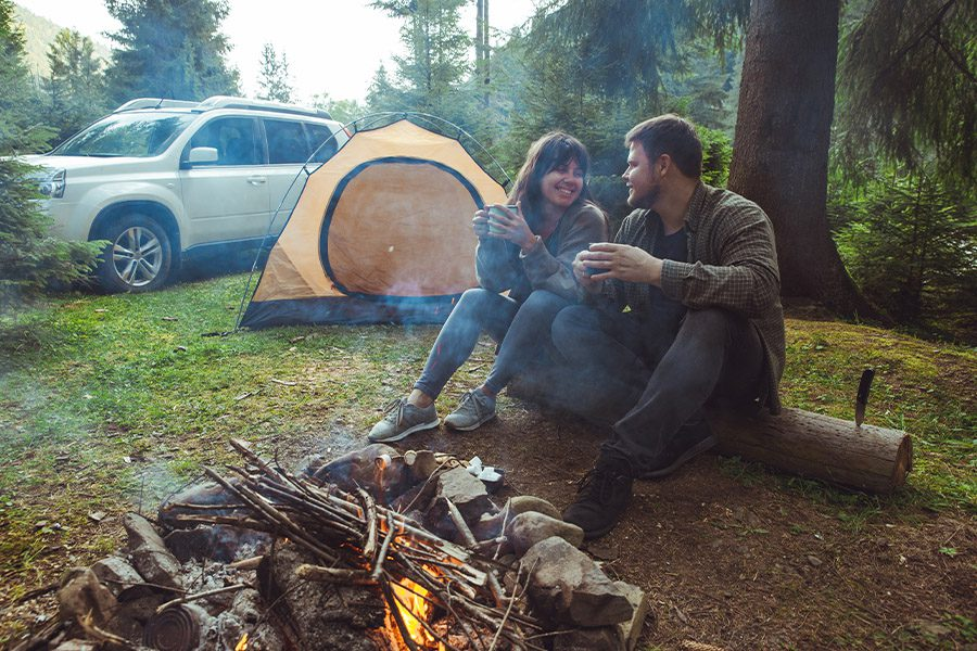 Contact - Couple Sitting Near Camp Fire and Drinking Tea Outdoors