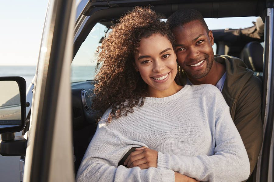 Personal Insurance - Young Couple Embracing by the Car Before Going for a Drive