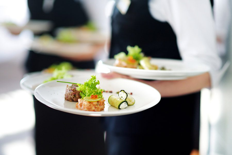 Specialized Business Insurance - Closeup of a Waiter Carrying Dinner Plates in a High End Restaurant