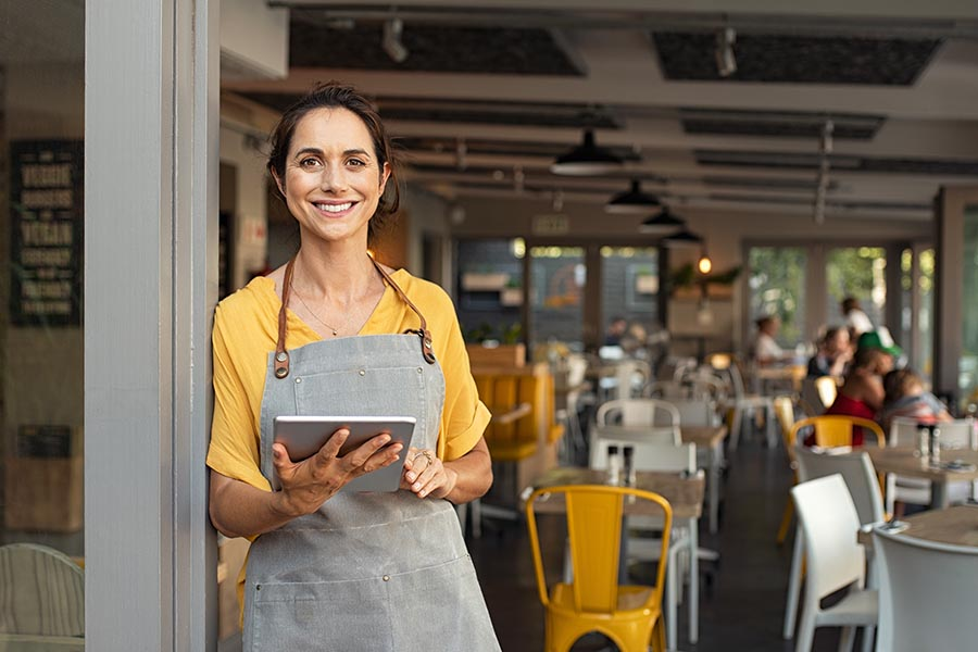Business Insurance - Restaurant Owner Smiles on Her Outdoor Dining Patio, Wearing an Apron and Holding a Tablet