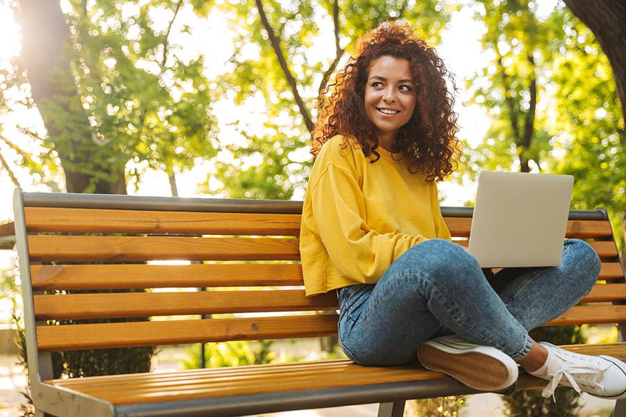 Client Center - Young Woman Uses a Computer on a Bench in a Small Town Park, Smiling Under the Trees