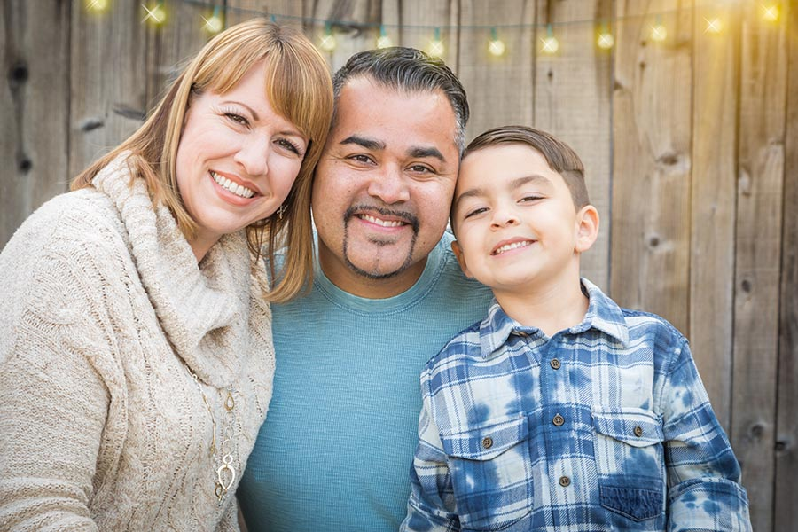Personal Insurance - Mother, Father and Young Son Smile in Their Backyard Patio With Twinkling Lights Behind Them on a Wooden Fence