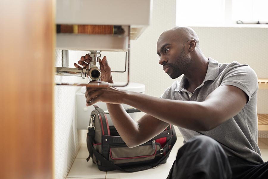 Specialized Business Insurance - Plumber Repairs Pipes Under a Sink, His Work Bag Nearby