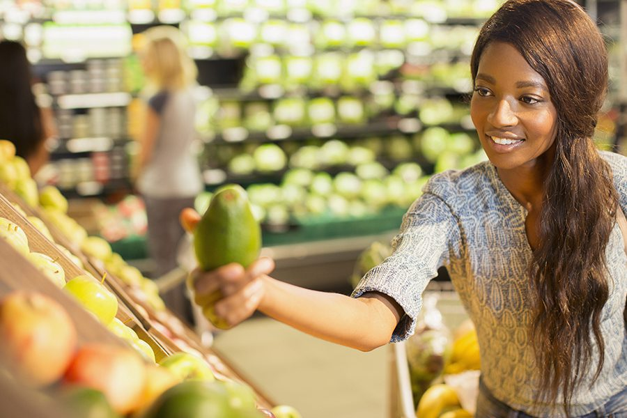 Grocery Store Insurance - Young Woman Shopping for Produce in a Grocery Store