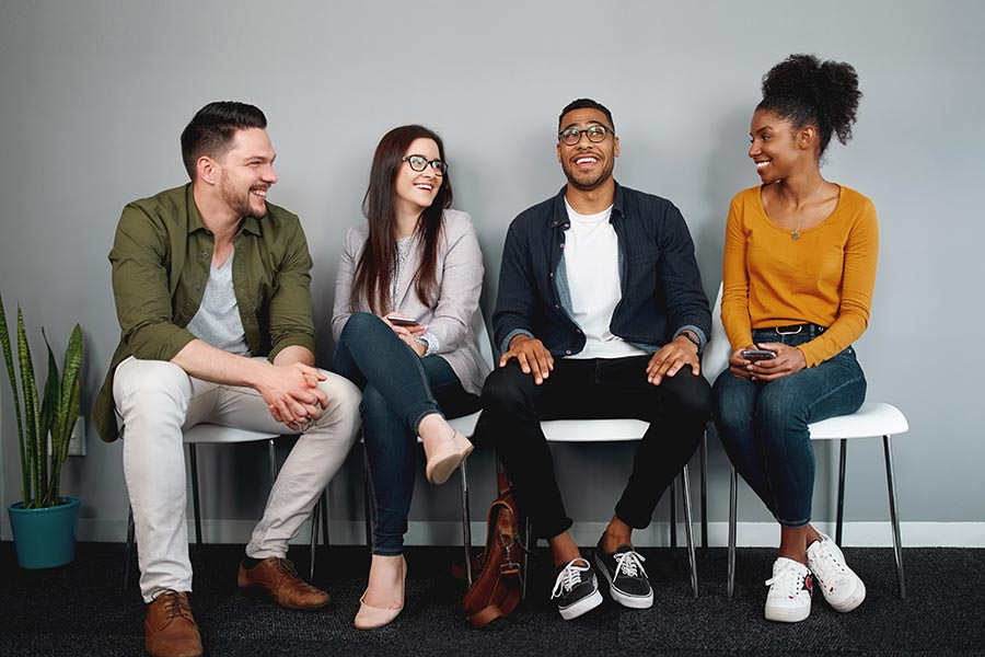 Employee Benefits - Four Coworkers in Business Casual Clothing Sitting in Chairs Against a Wall, Chatting Together