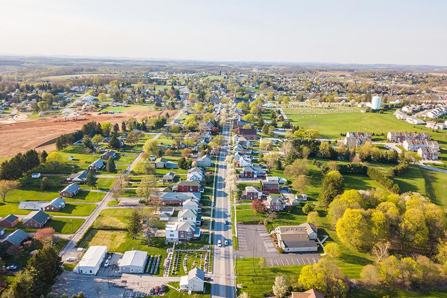 Harleysville, PA Insurance - Aerial View of a Suburban Area, With Homes and Businesses Surrounded by Trees, a Hilly Landscape in the Distance