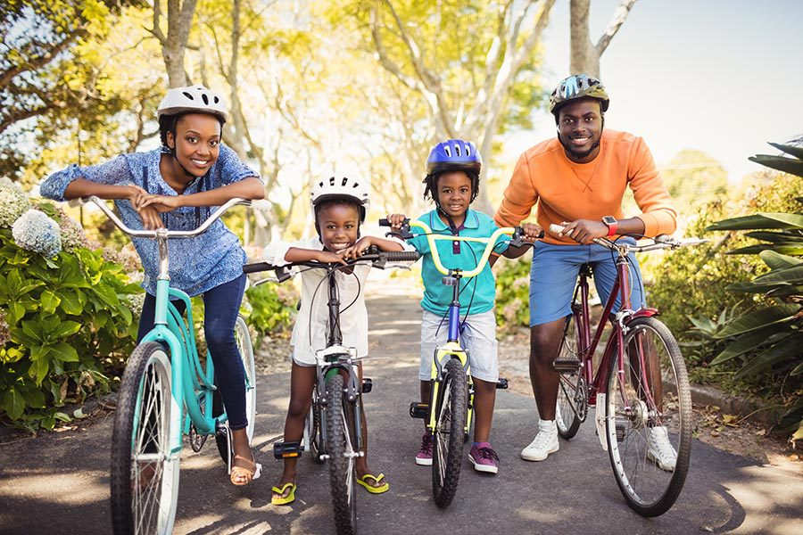 Personal Insurance - Family of Four Pauses on a Bike Ride in a Green Park, Everyone Smiling and Wearing Brightly Colored Clothing and Helmets