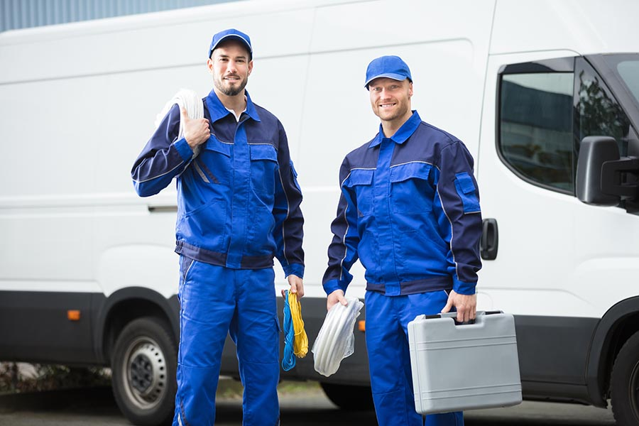 Specialized Business Insurance - Two Contractors Stand in Front of Their White Service Van, Wearing Blue Coveralls and Holding Tools
