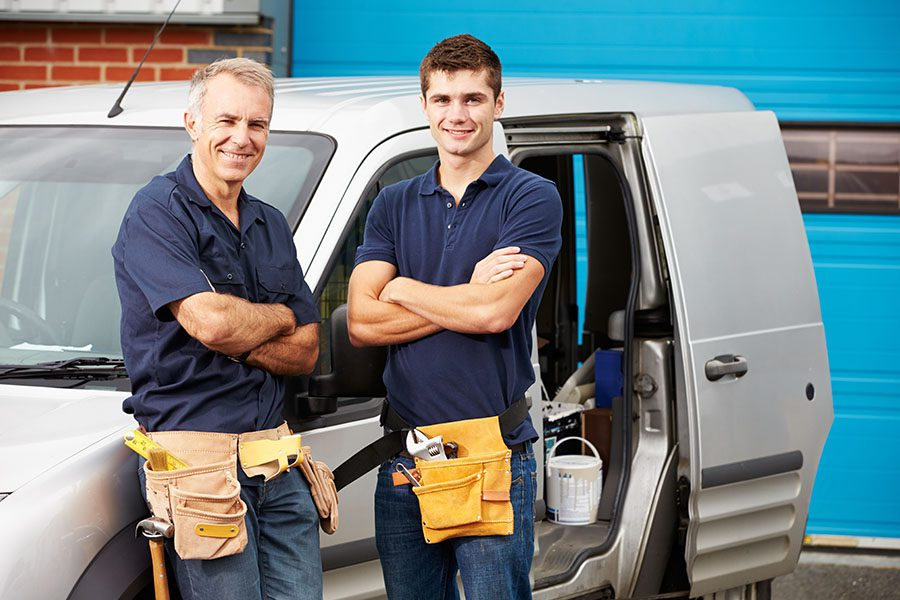 Business Insurance - Portrait of Two Smiling Contractors Standing Next to Their Work Van Outside