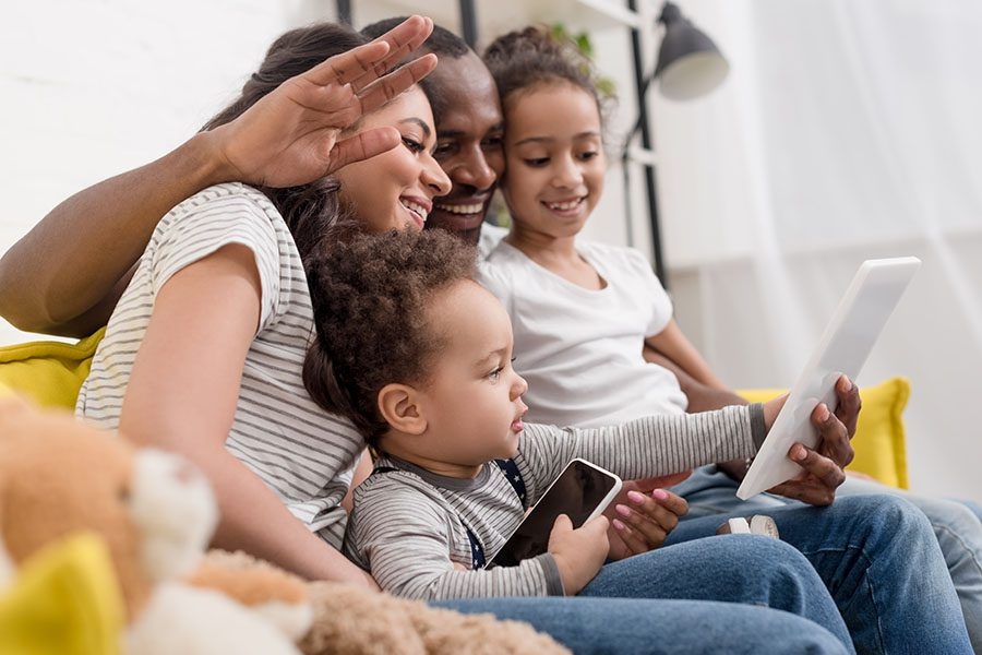 Client Portal - Portrait of a Cheerful Family with Two Kids Sitting in the Living Room Using a Table to Video Chat