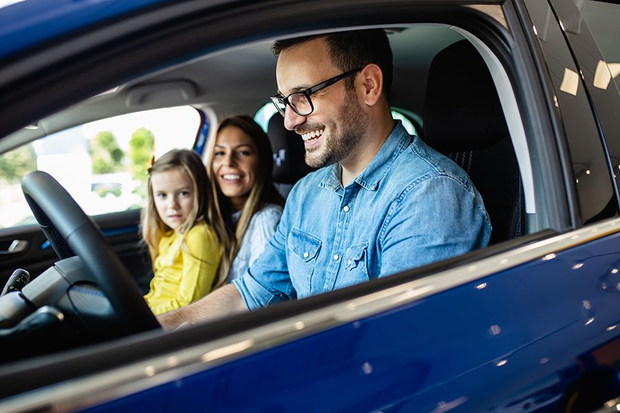 Insurance Quote - Closeup View of a Cheerful Family with a Young Daughter Sitting in a Car Getting Ready to Go on a Trip