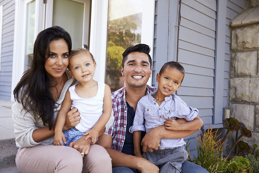 Personal Insurance - Portrait of a Happy Family with Two Kids Sitting on the Steps in Front of Their House