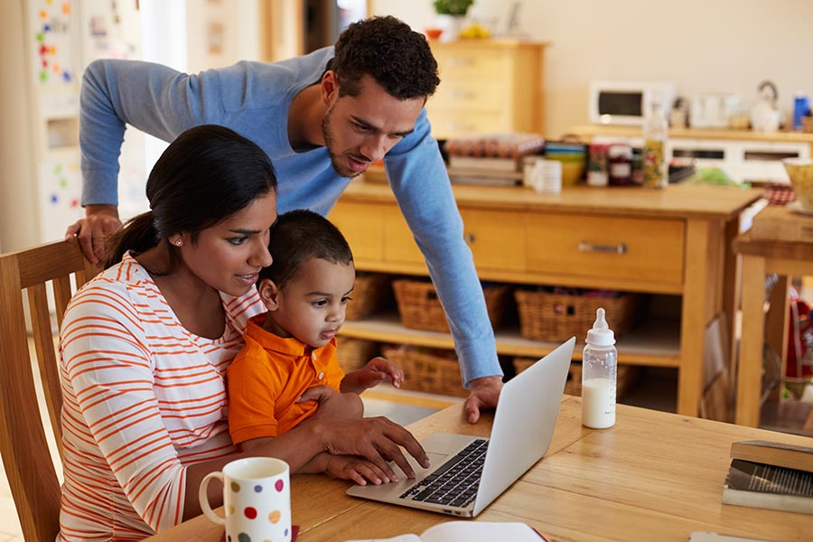 Client Center - Mother, Father and Young Son Use a Laptop at Their Kitchen Table, a Baby Bottle and Cup of Coffee Handy