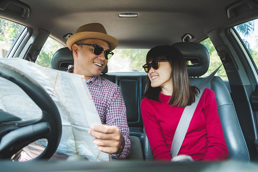 Contact Us - Happy Couple Look Over a Map in Their Car, Wearing Sunglasses, Ready for a Road Trip