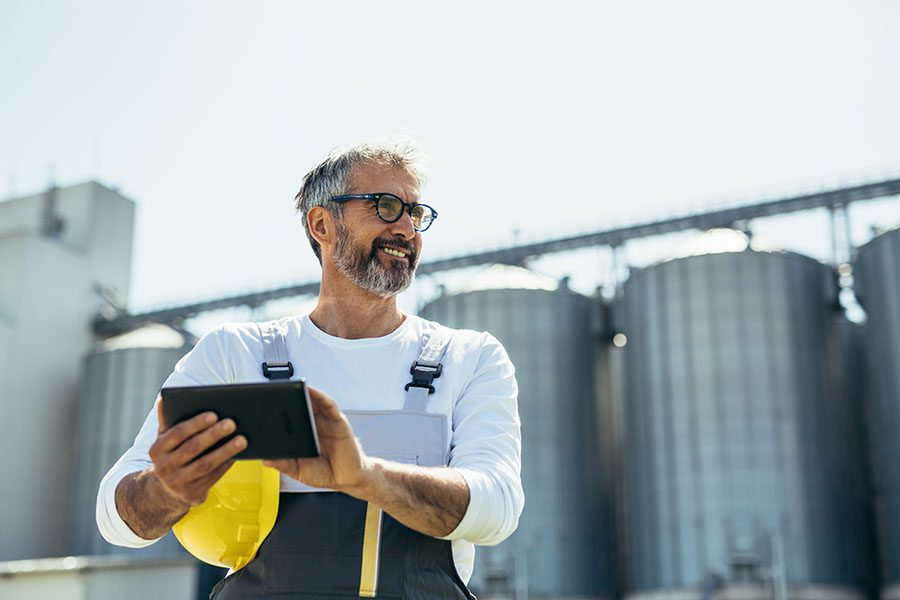 Insurance Quote - Closeup Portrait of a Cheerful Contractor Using a Tablet Standing in Front of Grain Silos