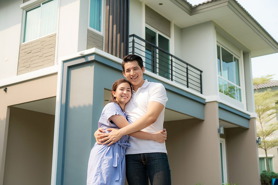 Personal Insurance - Smiling Portrait of Young Married Couple Standing in Front of Their New Home
