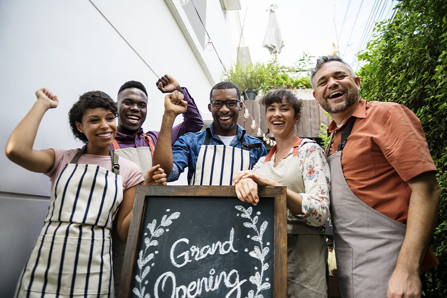 Business Insurance - Happy Staff Standing Behind Grand Opening Sign of Small Restaurant