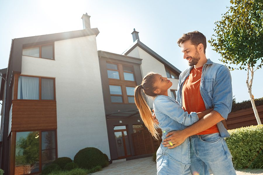 Personal Insurance - Young Couple Standing in Front of New House Together at Dusk