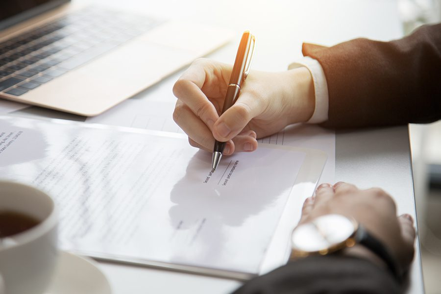 Tag and Title Services - Businessman Signing Vehicle Registration Documents on a Desk
