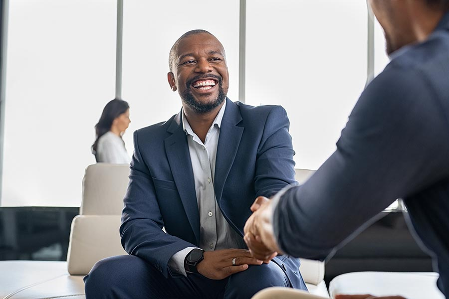 Business Insurance - Two Businessmen Shake Hands in the Large Open Space of an Office Building, Smiling and Wearing Nice Suits
