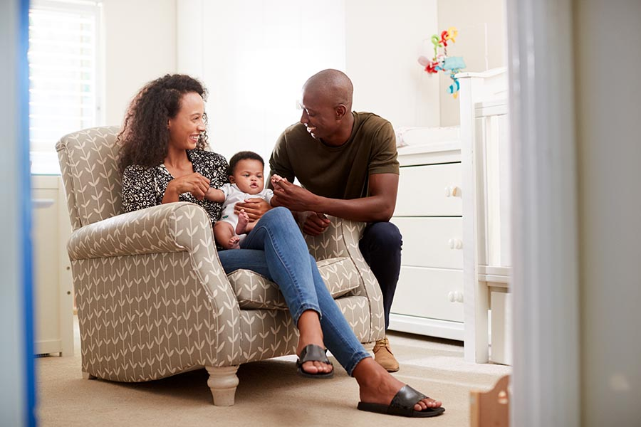 Contact Us - Mother and Baby Sit in a Rocking Chair, Father Crouched Next to Them, Admiring the Baby as the Parents Smile